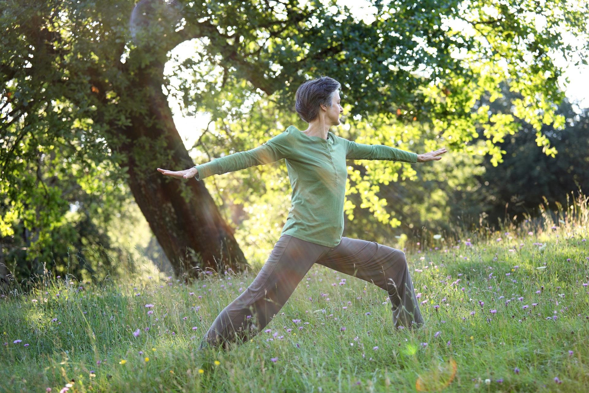 Yogaposition der Krieger: Simone Finger zeigt das Asana virabhadrasana 2 in der freien Natur. Komm in deine Kraft!